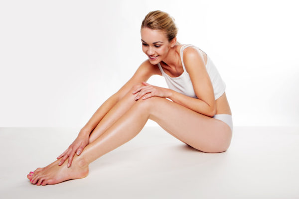 blonde woman sitting on the floor caressing her smooth legs